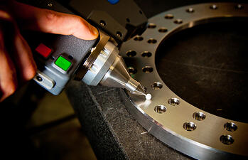 Round, CNC machined metal part during inspection with close-up of handheld inspection device