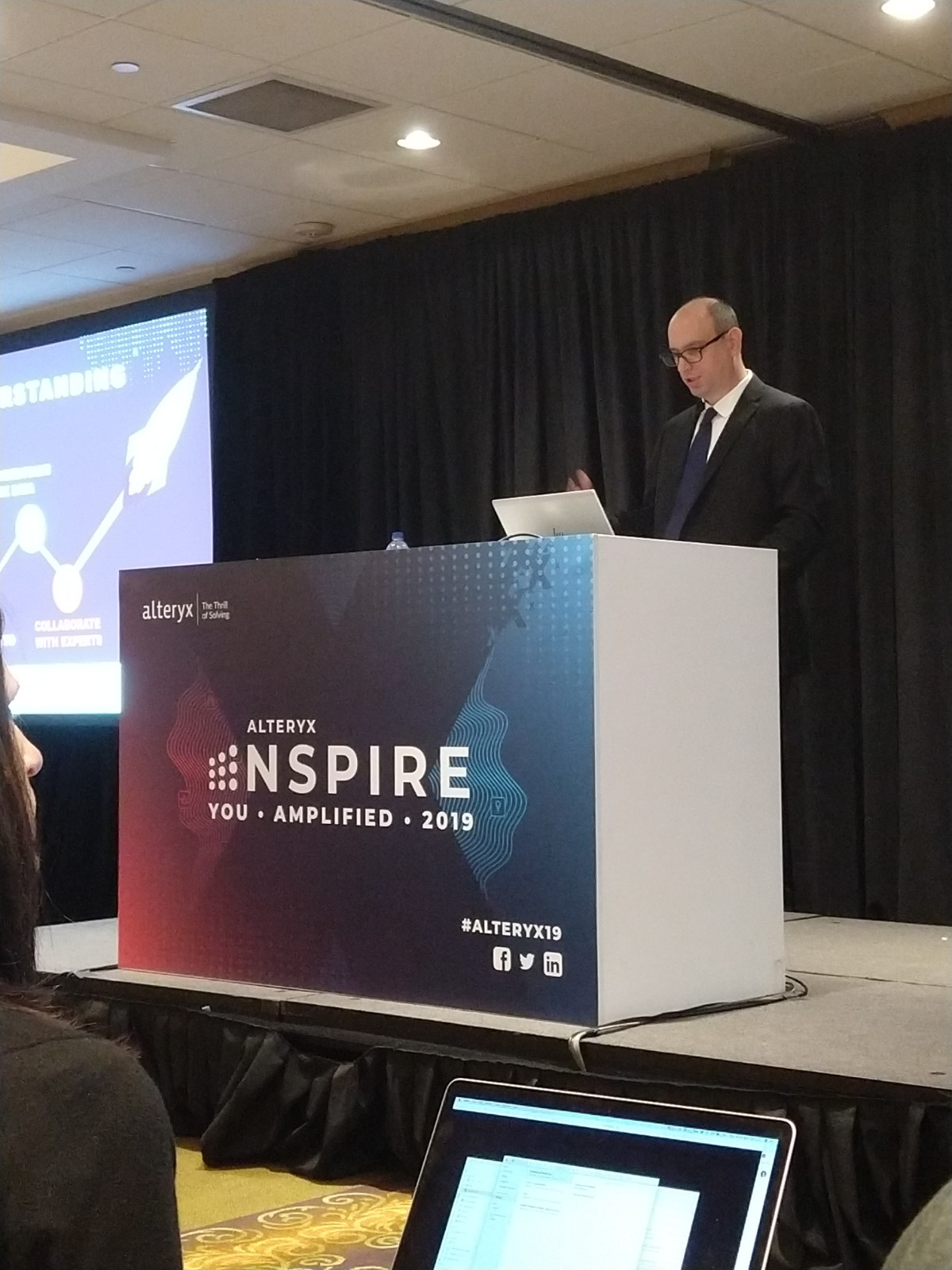Man speaking on stage with podium during breakout session of the Alteryx Inspire Conference 2019