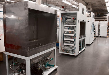Three white machines in different stages of production
