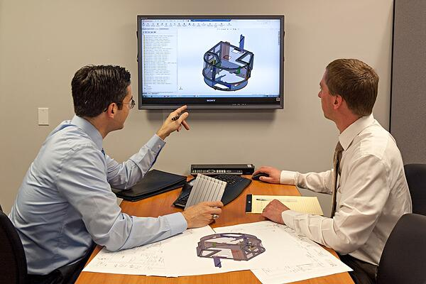 Two Engineers reviewing a design in a meeting room, on screen, with prints out on a table.
