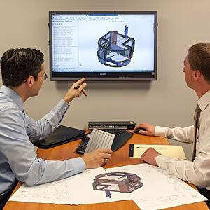 Meeting with engineers reviewing design on screen