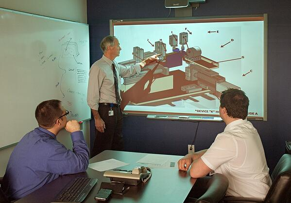 Three men reviewing a design on screen in a meeting room