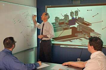 Meeting with engineers reviewing a design on screen