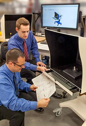 Two engineers reviewing a design's print with two machines