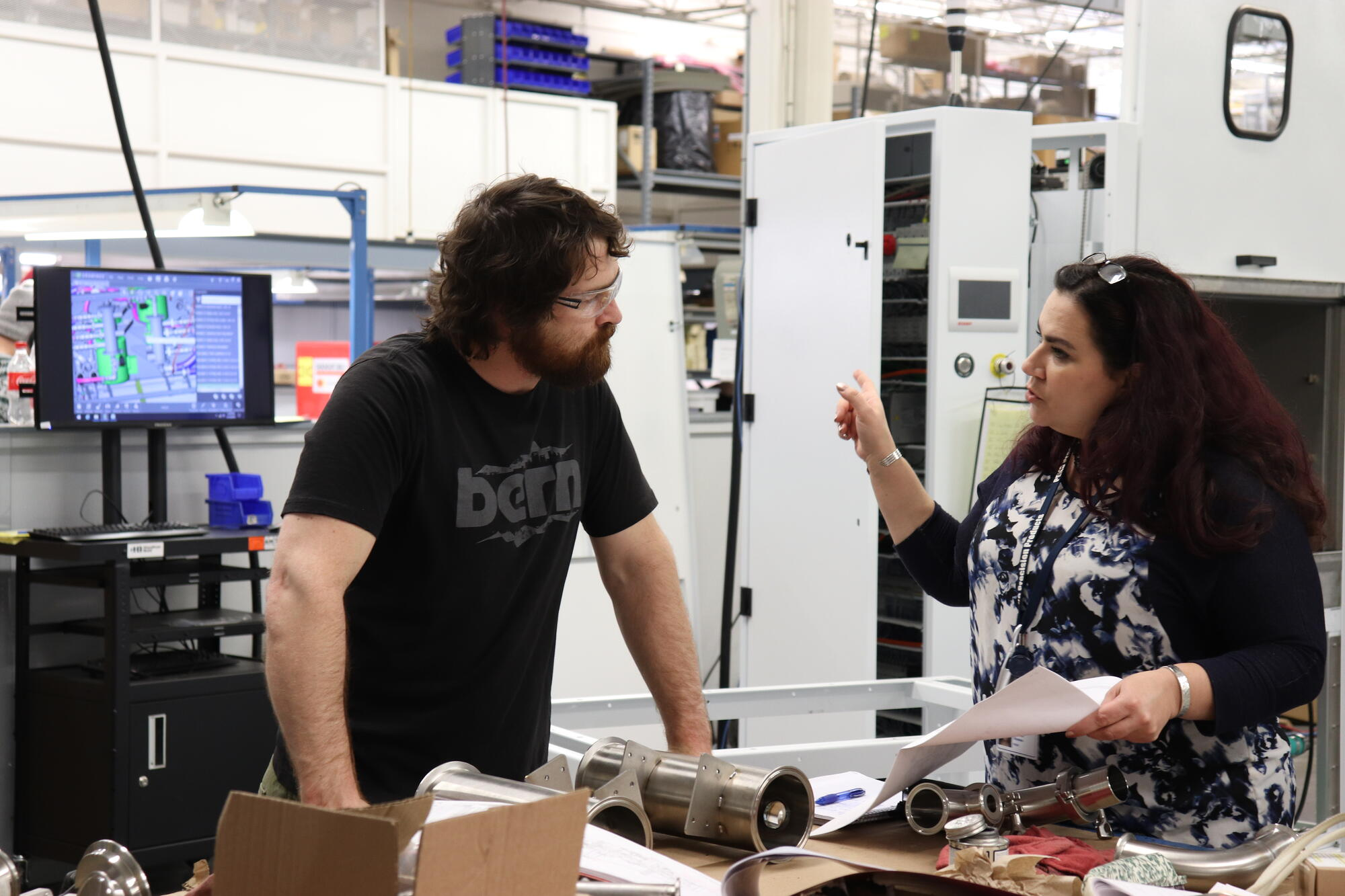 Female Industrial Engineer works with assembler on work instructions.