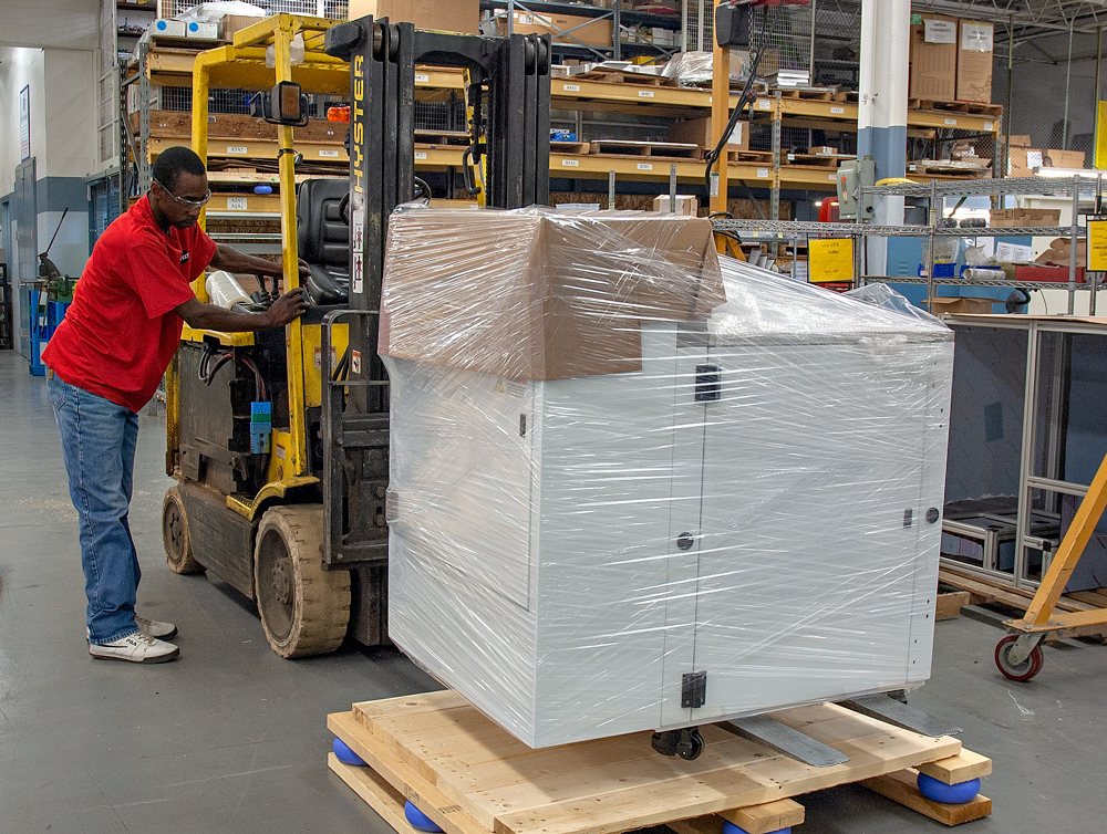 Worker packaging a white machine onto a forklift to ship to product's end user