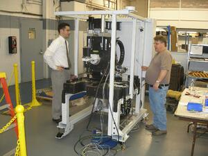 Engineer and assembler standing by beginning stages of a large machine's build