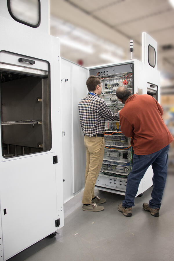 Two workers reviewing electrical wiring for a tall white machine