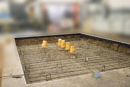 Dug out pit in factory floor with rebar to hold machine down