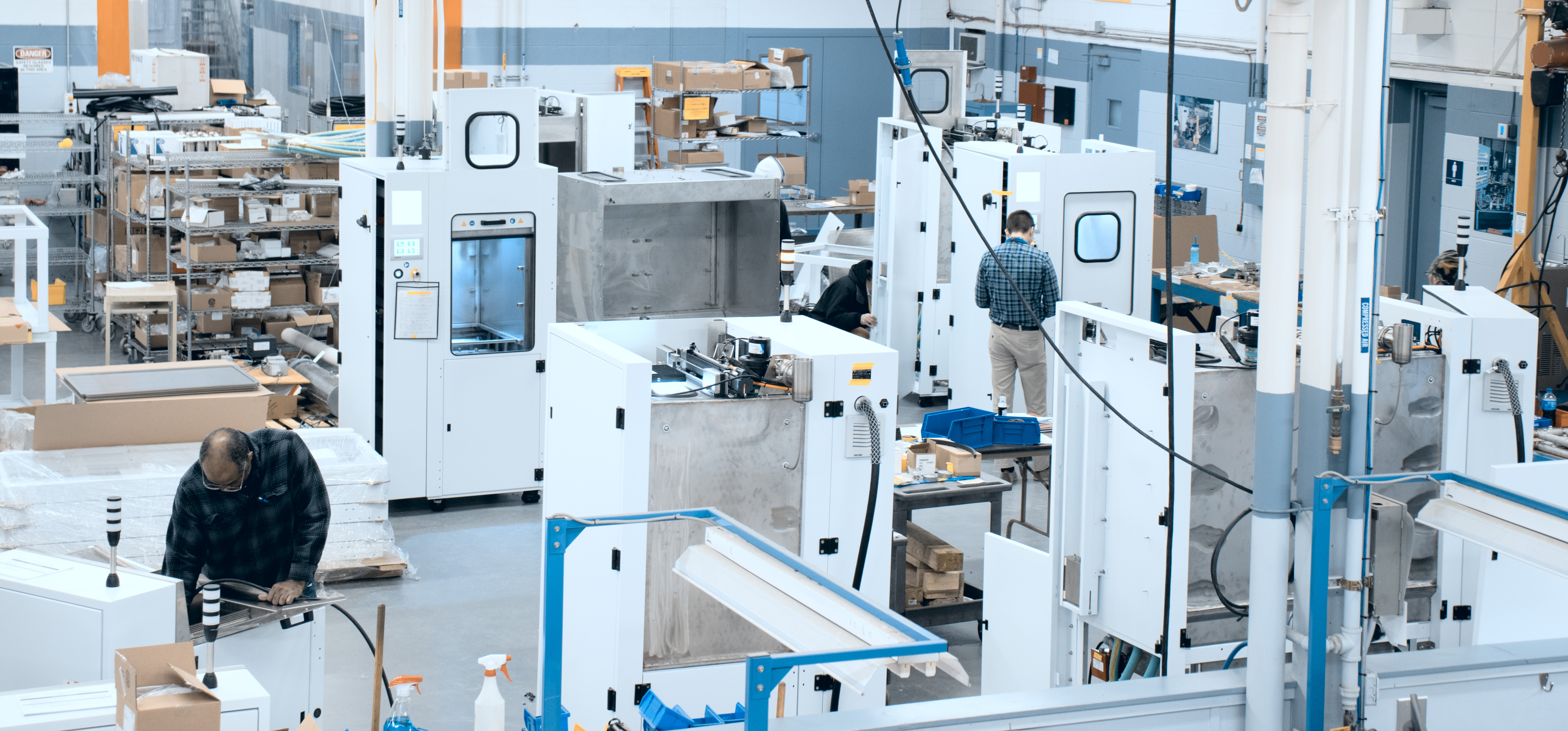Four large white machine builds on the manufacturing floor with assemblers