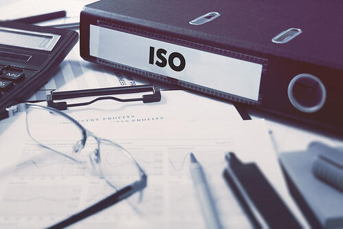 Office folder with inscription ISO - International Organization for Standardization - on Office Desktop with Office Supplies. Business Concept on Blurred Background. Toned Image.-1