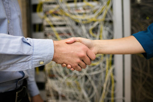 Technicians shaking hands in server room at the data centre